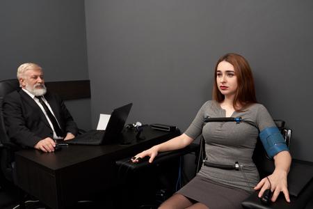 Schöne Frau sitzt im schwarzen Stuhl mit Sensoren an Fingern, Händen und Körper des Lügendetektors. Älterer Mann im schwarzen Anzug, der am Tisch sitzt und Computerpolygraphen betrachtet, Frau testet.