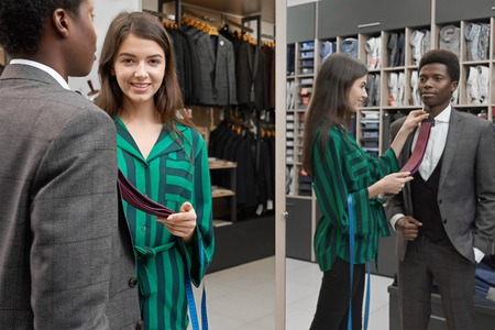Young african man standing in shop, looking at mirror, choosing tie. Girl shop consultant helping client to choose necktie and smiling. Man wearing in grey suit and white shirt. Imagens