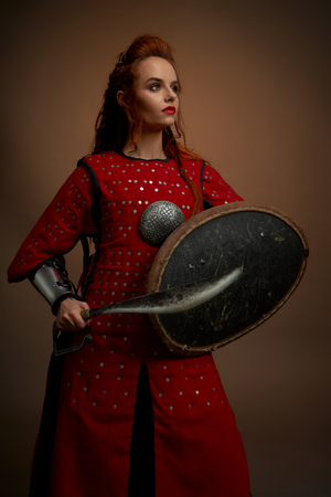 Beautiful, brave woman wearing in red medieval tunic holding shield and dagger. Serious, young woman with ginger hair looking away, posing in studio on solid background.