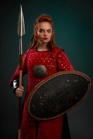 Female model looking at camera, holding spear and shield. Beautiful, brave and serious woman wearing in red medieval costume, tunic. Woman with ginger hair standing, posing in studio. Stock fotó