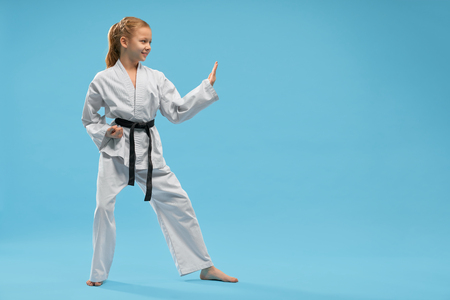 Side view of smiling girl wearing white kimono looking forward and training karate on blue isolated background. Active child doing sport and practising taekwondo. Concept of martial arts and combat.