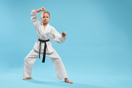 Angry female fighter in white kimono practising karate and jujitsu on blue isolated background. Sporty girl standing in stance and training in studio. Concept of martial arts and combat. Imagens