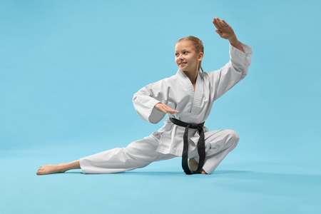 Cheerful little sports woman sitting on twine and practising karate on blue isolated background. Active girl wearing white kimono and black belt doing sport in studio. Concept of karate and jujitsu. Stock Photo - 122678556