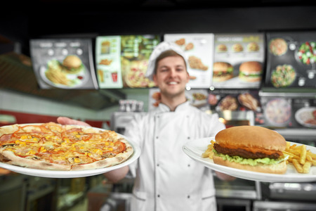 Selective focus of tasty pizza and haumburger with free potatoes in hands of professional male cook in pizzeria. Happy chef in white uniform cooking fast food in cafe. Concept of junk food. Imagens