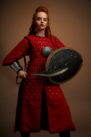 Front view of female gladiator warrior in armor keeping big knife and shield and looking at camera on isolated background in studio. Strong fighter in armor posing. Concept of weapon and power.