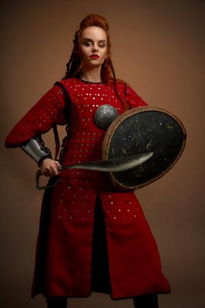Vorderansicht des weiblichen Gladiatorenkriegers in Rüstung, der großes Messer und Schild hält und die Kamera auf isoliertem Hintergrund im Studio betrachtet. Starker Kämpfer in Rüstung posiert. Konzept der Waffe und Macht.
