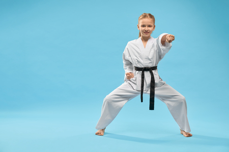 Front view of female teenager standing in stance and punching on blue isolated background. Smiling girl looking at camera and posing in studio. Child fighting and exercising karate. Concept of sport.