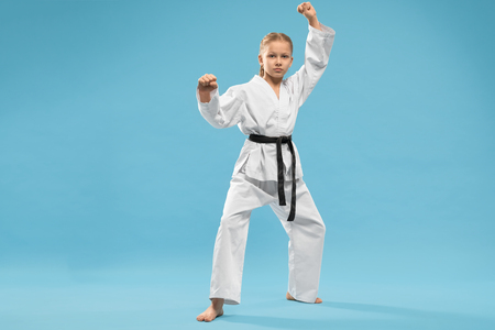 Front view of serious girl in kimono doing karate and looking at camera on blue isolated background. Strong child standing in stance and posing in studio. Concept of martial arts and combat.