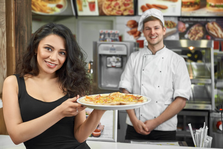 Happy female customer keeping tasty pizza in hands and posing in cafe. Attractive brunette looking at camera and smiling while professional male cook standing at background. Concept of pizzeria.