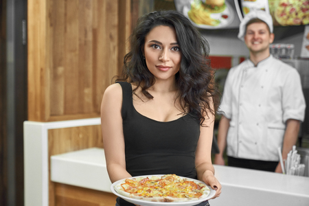 Satisfied female client of cafe buying delicious pizza. Attractive brunette keeping food in hands, looking at camera and posing. Pretty woman enjoying lunch in pizzeria. Concept of consuming.