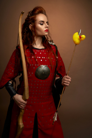 Female fighter in red armor keeping dow and rubber duck and posing on isolated background. Young red haired warrior looking at toy in studio. Strong woman looking at arrow. Concept of power.