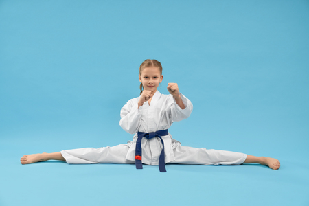 Front view of little sports woman sitting on cross twine and looking at camera in studio. Strong girl in white kimono posing on blue isolated background. Concept of karate and martial arts. Imagens