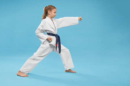 Side view of concentrated girl in kimono standing in stance and doing karate in studio. String child looking forward and exercising on blue isolated background. Concept of martial arts. Imagens
