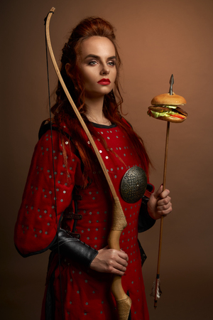 Portrait of determined female fighter in red armor keeping bow and arrow with hamburger in studio. Spartan warrior looking aside and posing on isolated background. Concept of power and food.