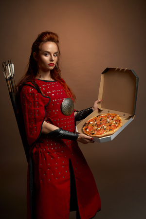 Side view of young female fighter in armor keeping tasty pizza on isolated background in studio. Strong warrior with bow and arrow looking at camera and posing. Concept of food of heroes.