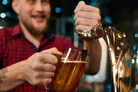 Selective focus of male hands keeping pint and pouring beer in pub. Young bearded barmen in checkered shirt with tattoo working and servicing people in bar. Concept of ale and job.