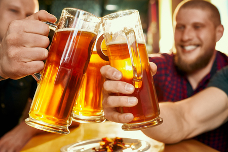 Closeup of glasses of beer in hands of happy company in pub. Cheerful male friends keeping pints of ale, toasting and laughing in bar on weekends. Concept of vacation and beverage.