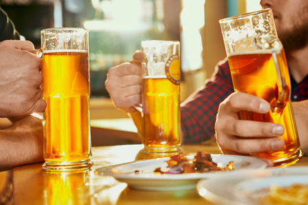 Selective focus of glasses of ale standing on table in pub. Strong male company keeping pints, drinking beer,  eating snacks and talking in bar. Concept of beverage and alcohol.