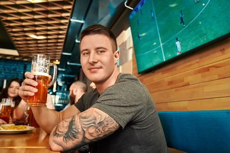 Side view of handsome man with tattoo drinking beer, looking at camera and smiling in bar. Young male posing while resting with friends in pub on weekends. Concept of leisure and fun.