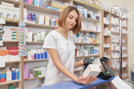Concentrated woman scanning price of medicament with special barcode scanner. Specialist using device, holding white medical box. Woman working in pharmaceutical industry.