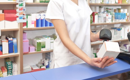 Unrecognizable worker of drugstore standing at counter at workplace. Woman scanning barcode of medicament with special scanner. Pharmacist in white unifrom holding white medical box. 版權商用圖片
