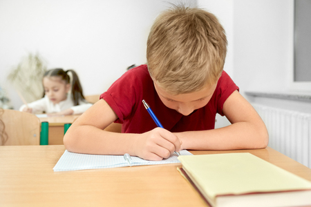 Young schoolboy in red t shirt looking down, sitting at desk and writing with pen in copybook. Concentrated pupil, teenager of primary school at table in classroom.