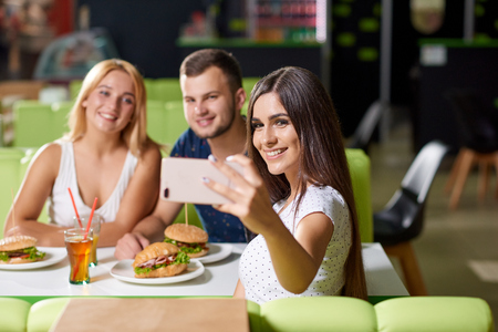 Beautiful cheerful girl keeping phone and taking selfie with friends sitting opposite in cafe. Smiling company looking at phone and posing while resting. Concept of eating and tasty fast food. 写真素材