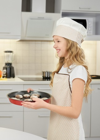 Charming, cute little girl holding metal square baking form with homemade chocolate cookies. Cheerful, happy teenager wearing in chef hat and apron, smiling, looking away.