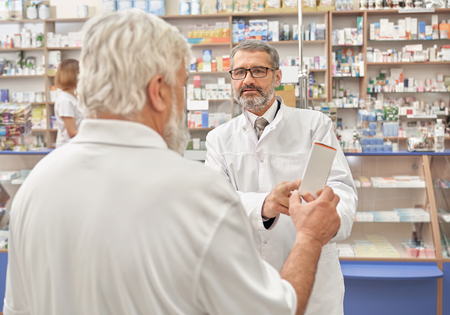 Pensioner talking with doctor about medicines and treatment of disease. Specialist explaining, helping elderly man with choice of medicament. Doctor wearing in white lab coat. 免版税图像 - 122665276