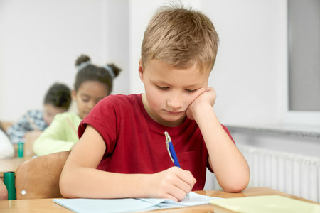 Primary schoolboy sitting at desk, looking down, leaning head on hand and writing with blue pen in copybook in classroom. Portrait of young, diligent schoolchild in class. Imagens