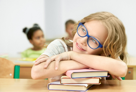 Beautiful, cute schoolgirl, teenager sitting at desk in classroom, leaning on stack of books, looking away. Pretty pupil of primary school posing in room of school, smiling.