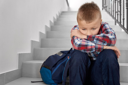 Disappointed, sad schoolboy of primary school with backpack sitting on stairwell. Handsome, depessed schoolchild wearing in checked shirt leaning head on hands. Stockfoto