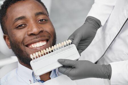 Giovane africano che guarda l'obbiettivo e sorride mentre il dentista mantiene la gamma di otturazioni in clinica. Paziente felice che si gode un bel sorriso bianco mentre visita l'ufficio del dentista. Concetto di cura.
