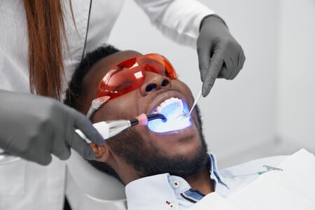 African man lying on dentist chair with open mouth in protective glasses while female dentist doing filling with ultraviolet light. Man visiting doctor curing teeth in clinic. Concept of stomatology. 写真素材