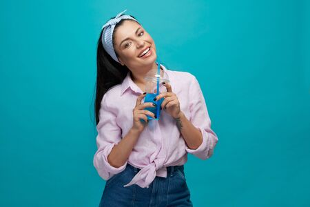 Charming, positive girl holding transparent plastic cup with blue fizzy drink. Beautiful, happy model in stylish trendy clothes, posing on blue background, looking at camera, smiling. Standard-Bild