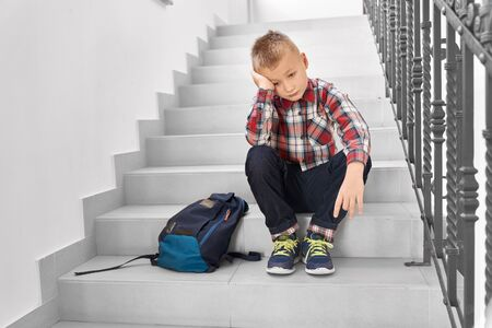 Front view of sad blond boy sitting on stairs in corridor of school and leaning head by hand. Little disappointed pupil thinking about his bed behavior on lesson. Concept of study.