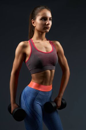 Mujer atlética con el pelo castaño atado en un nudo vistiendo leggings deportivos de moda y sujetador haciendo ejercicios con pesas pesadas negras. Chica joven y atractiva con piel bronceada bombeando bíceps en el interior