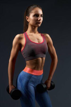 Sportliche Frau mit braunen Haaren, die in Knoten gebunden sind und modische Sportleggings und BH tragen, die Übungen mit schwarzen schweren Hanteln machen. Junges attraktives Mädchen mit gebräunter Haut, das Bizeps drinnen pumpt
