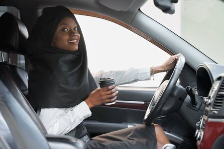Cheerful african woman holding hand on steering wheel and coffee cup while driving car. Beautiful young muslim woman in black hijab sitting in car, looking at camera.