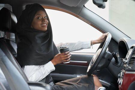 Fröhliche afrikanische Frau, die Hand am Lenkrad und Kaffeetasse hält, während sie Auto fährt. Schöne junge muslimische Frau im schwarzen Hijab, die im Auto sitzt und Kamera betrachtet.