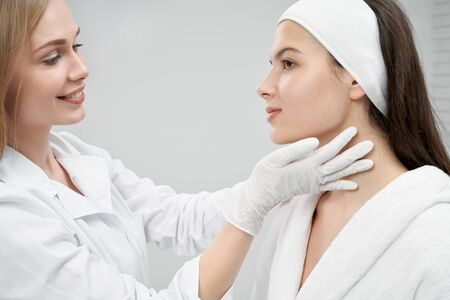 Young, pretty woman on advice in cosmetology cabinet. Positive doctor professional inspecting face of patient, touching with hands in white medical gloves. Cosmetologist and client on grey background.