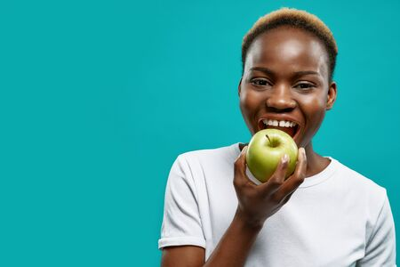 Beautiful, positive african woman with perfect white teeth biting green apple. Handsome, charming girl in white t shirt posing on blue background with copy space. Stock Photo