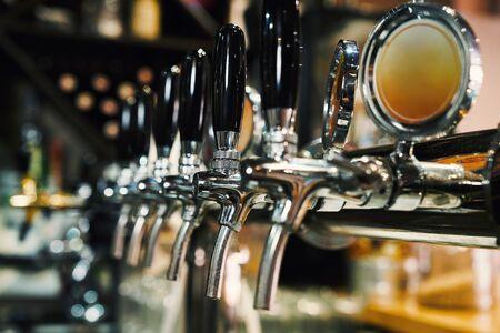 Nahaufnahme von Bierhähnen in Reihe. Metallische Ausrüstung für Bars und Minibrauereien. Konzept der modernen Ausrüstung. Standard-Bild