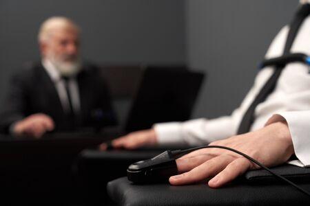 Primo piano dell'indicatore di impulso sulla mano maschio durante il test della macchina della verità. Adulto che passa l'esame della menzogna e risponde mentre l'uomo in abito nero intelligente controlla il processo e controlla il risultato sullo sfondo. Archivio Fotografico