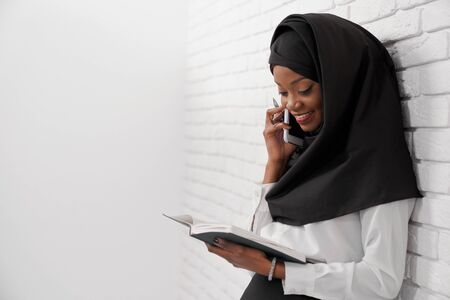 Cheerful muslim woman standing leaning at white wall, holding notebook and talking by phone. Office worker of company in black hijab looking at notebook, smiling. Stok Fotoğraf