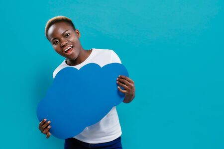 Beautiful, attractive afro woman standing and holding blue paper speech bubble in form of cloud. Positive, stylish girl in white t shirt and jeans on blue background.
