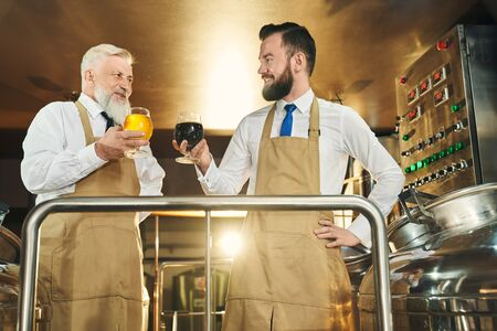 Two successful brewers standing on metal platform and holding beer glasses. Positive, cheerful brewery workers looking at each other, posing and smiling.