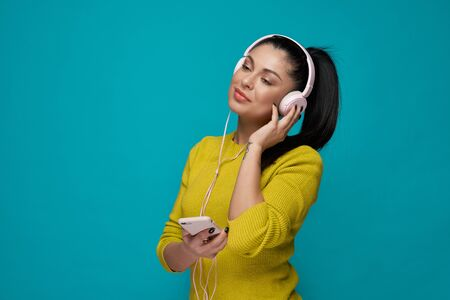 Beautiful, charming model with pony tail listening music in headphones. Pretty, elegant girl in yellow jumper holding white phone, posing on blue background, looking away. Stockfoto