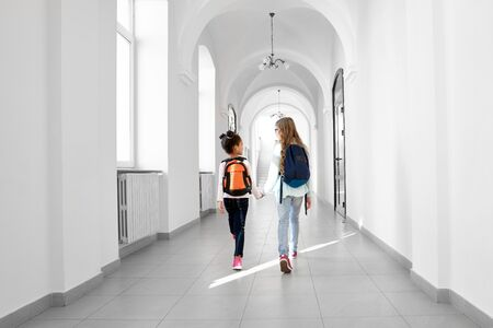 Back view of two girls going forward at school corridor with backpacks on back. Two school girl friends going home from lessons. Concept of study in beautiful school.