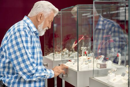 Side view of senior man with grey hair and heard wearing checkered shirt standing near showcase with luxury jewelry on modern store. Male customer shopping at the boutique